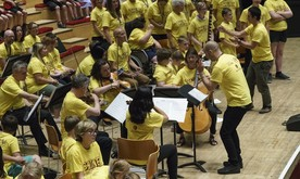 A mid-short of a large group of musicians on stage, all in yellow t-shirts.