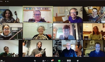 A zoom meeting with twelve participants smiling, some holding orchestral instruments.