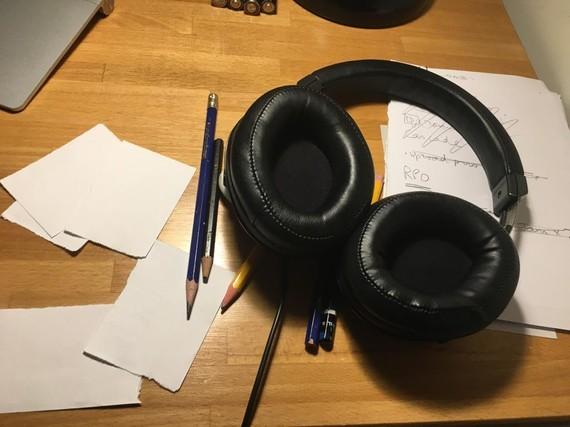 Headphones, pencils, and scraps of paper on a desk