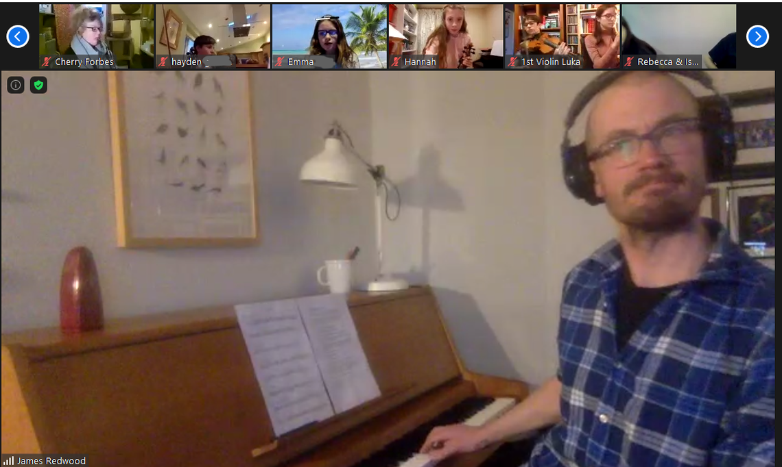 A man plays piano on a Zoom call to several people.