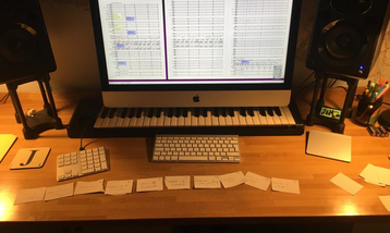 A desk with a computer, a musical keyboard, and lots of paper notes