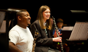 A black man with a clarinet sits next to a white girl with a clarinet, both are smiling