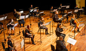 A group of young and older musicians sat socially distanced on a stage