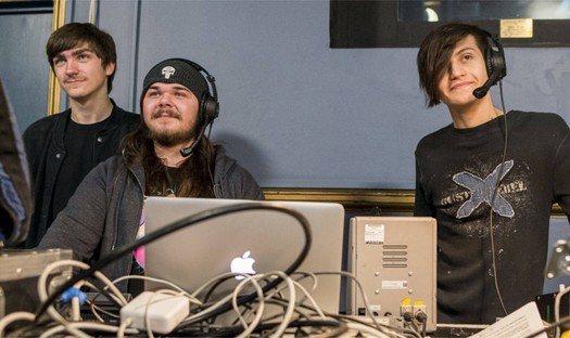 Three boys sat at a technical sound desk, two wear a microphone headset..