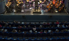 A audience of school children sat in theatre seating watching an orchestra perform on stage.