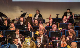 Two young producers dressed as a bee and lion present in front of an orchestra. A screen behind shows a musical score.