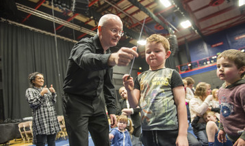 A conductor showing a young boy how to conduct with a baton.