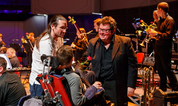 A young man in a wheelchair and his carer talk to a musician from the orchestra.