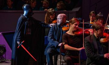 A young producer dressed as Darth Vader puts his hand on the shoulder of a violin player who looks afraid.