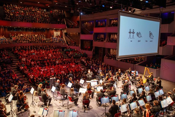 A full orchestra on stage performing to an audience of hundreds of school children, with a big screen overhead.