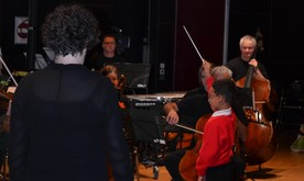 A young boy conducts the orchestra.