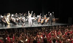 A presenter on stage in front of the orchestra waving to a large audience of children.