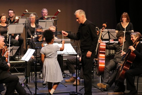 The conductor hands a young girl a baton as she step up to conduct the orchestra.