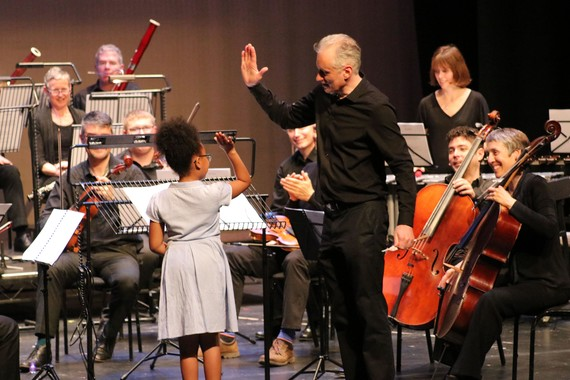 A young girl on stage receiving a high-five from the conductor